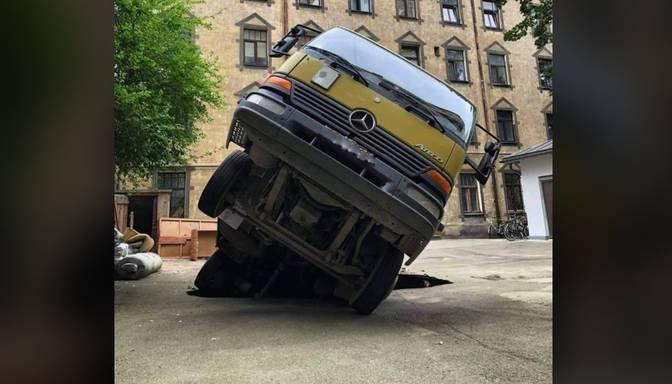 Rīgā asfaltā daļēji iegruvusi automašīna