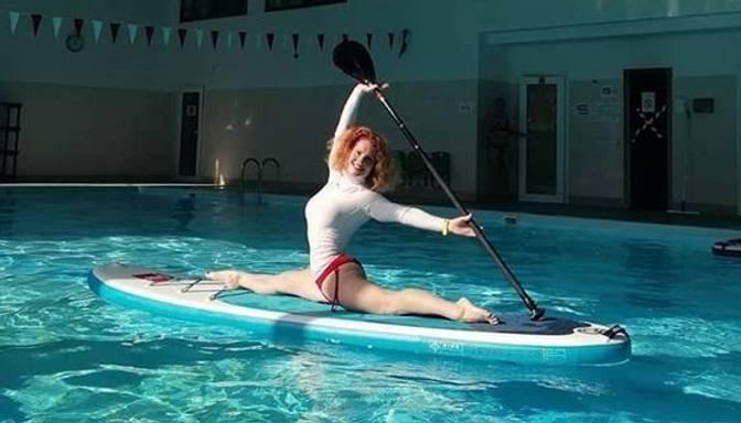Ieva Brante demonstrē izcilu lokanību un līdzsvara izjūtu, nostājoties špagatā uz SUP dēļa